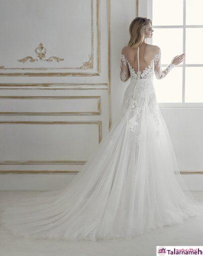 یک لباس عروس با مدل عجیب. دامنی طراحی شده با تکه های توری و به صورت موج دریا. دارای آستین بلند با تورهای گیپور سفید گلدوزی شده که به توری رنگ بدن متصل شده و از ناحیه گردن به پشت اتصال دارد. دنباله آن قابلیت جداشدن دارد که خود یک مزیت برای فصل های سر سال می باشد. در قسمت پشت، با استفاده از مرواریدهایی زیبا، به یکدیگر وصل شده اند. یک لباس فوق العاده عاشقانه.